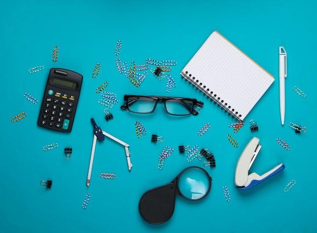 Bürowerkzeuge, schreibwaren. hefter, taschenrechner, lupe, büroklammern, notizbuch, kompass auf blau.