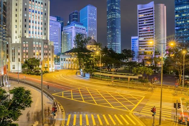 Bürowolkenkratzergebäude und beschäftigter verkehr auf landstraßenstraße mit unscharfen autolichtspuren.