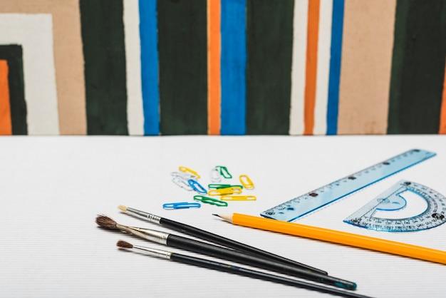 Bürsten und briefpapier nahe abstrakter malerei