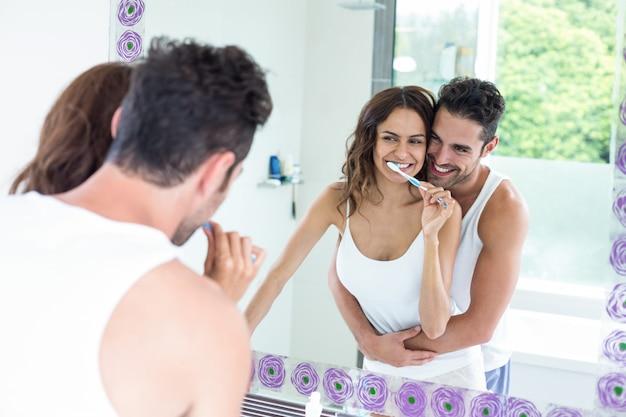 Bürstende zähne der frau während ehemann, der sie im badezimmer umfasst