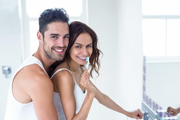 Bürstende zähne der frau während ehemann, der sie umfasst