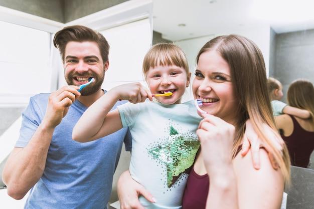 Bürstende zähne der glücklichen familie am morgen