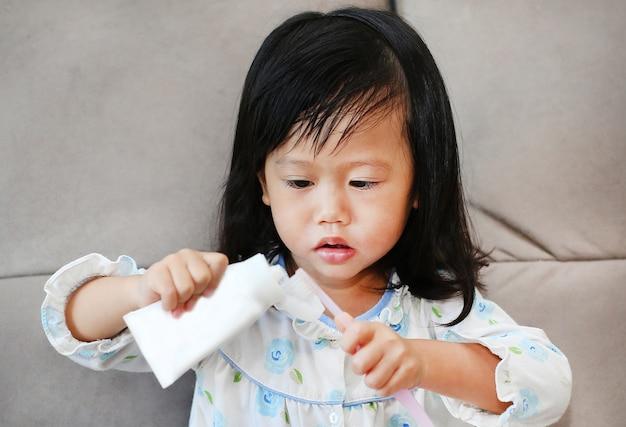 Bürstende zähne des asiatischen kindermädchens am morgen