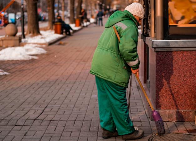 Bürstenstraßen des weiblichen straßenreinigers mit besen. frau besetzt zigarettenkippe