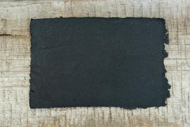 Büttenpapier, blatt liegt auf einem holztisch. platz für designertext, flachgelegt. das konzept des recyclings und der schaffung von schönem kunsthandwerk.