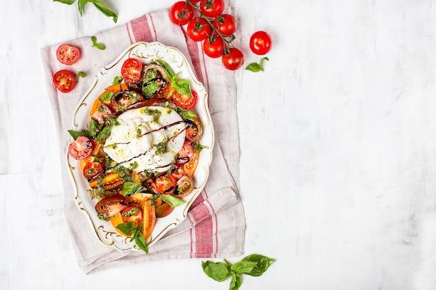 Buffalo burrata käse mit frischen rohen tomaten und basilikumblättern