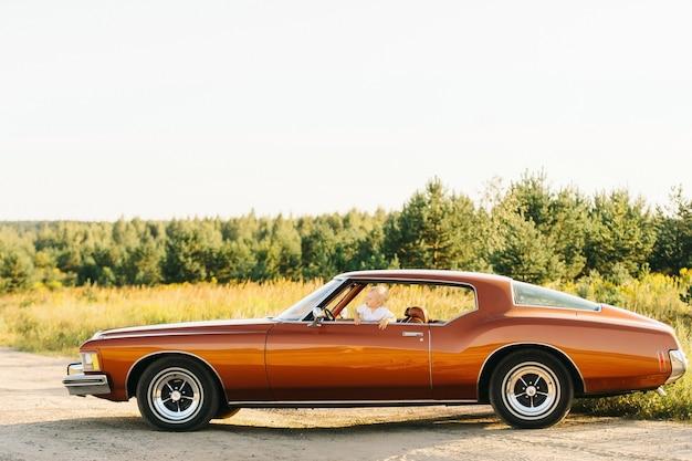 Buick rivierretro stil. einzigartiges auto. netter blonder junge guckt aus dem fenster des retro-autos