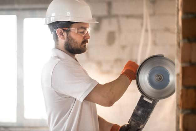 Builder arbeitet mit einem professionellen winkelschleifer, um ziegel zu schneiden