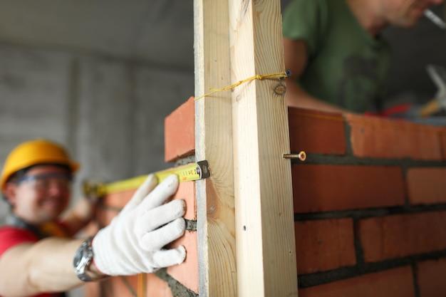 Builder führt messungen mit einem maßband auf mauerwerk durch.