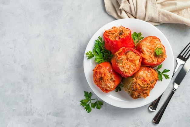 Bulgarischer pfeffer gefüllt mit fleisch, gemüse und reis auf grauem hintergrund. gesundes essen. ansicht von oben, kopienraum.