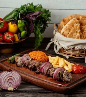 Bulgur fleischzwiebeln und pommes auf einem holztisch