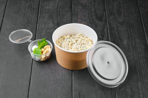 Bulgur-porridge mit mandel- und haselnüssen und preiselbeeren in zuckerpulverpanade in take-away-verpackung