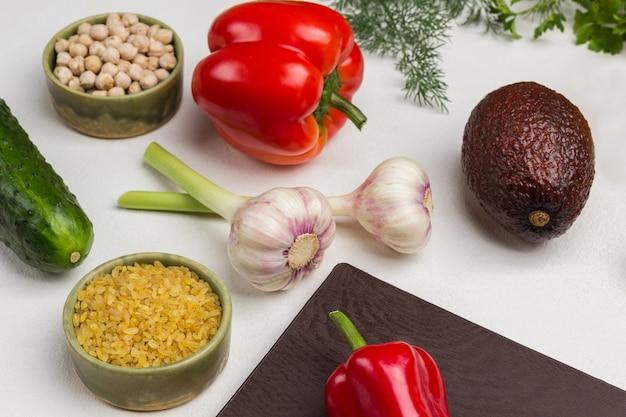 Bulgur und kichererbsen in schalen. knoblauch, pfeffer und avocado auf dem tisch. weißer hintergrund.