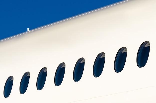 Bullaugen auf weißem modernem flugzeug und himmel