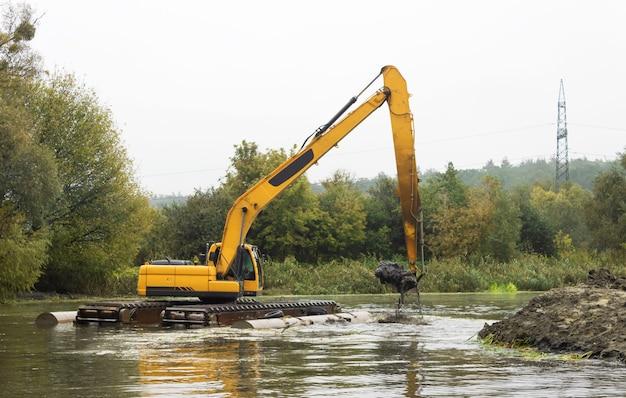 Bulldozer auf dem wasser gräbt den fluss, um den flusskanal zu vertiefen und freizumachen, um den fluss zu verbessern.