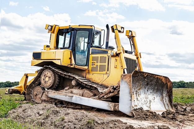 Bulldozer-maschine nivelliert baustelle. erdbewegungsmaschine mit raupe bewegt erde. nahaufnahme. bau schwere maschinen.