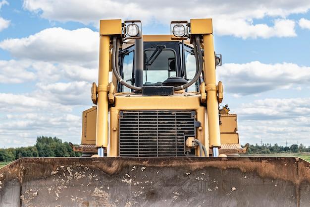 Bulldozer-maschine nivelliert baustelle. erdbewegungsmaschine mit traktor bewegt erde. nahaufnahme. bau schwere maschinen.