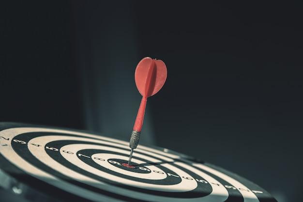 Bullseye hat einen pfeilpfeilwurf, der die mitte eines schießziels für geschäftsziele trifft.