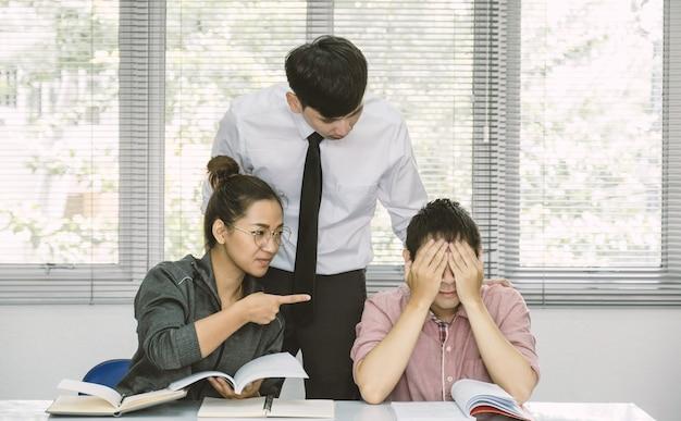 Bully woman point auf manngesicht im klassenzimmer lehrer kommt, um die schüler zurück zum schulkonzept zu trösten
