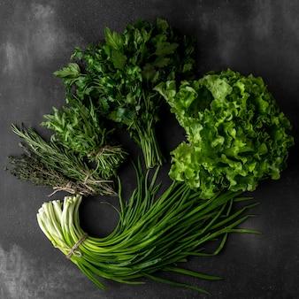 Bund grüne petersilie, frische zwiebeln oder schalotten, rucola, thymian, rosmarin auf dunklem hintergrund, draufsicht