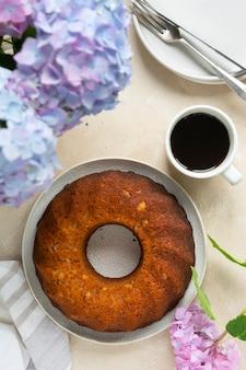 Bundt-kuchen, hausgemachter kuchen gebackener runder kuchen mit kaffeetasse, blumen auf hintergrund