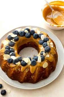 Bundt-kuchen mit erdnussbutter-glasur. gesunder zuckerglutenfreier kuchen mit chiasamen, dekoriert mit blaubeeren und mandelflocken.