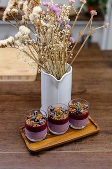 Bunt gesundes frühstück süße desserts wenige verschiedene chia pudding in gläsern auf holztisch in der küche zu hause.