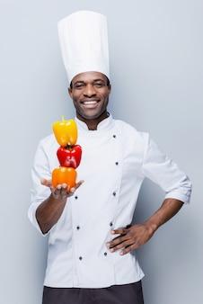 Bunt kulinarisch. selbstbewusster junger afrikanischer koch in weißer uniform mit mehrfarbigen paprikaschoten