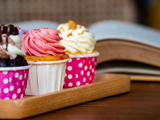 Bunt vom selbst gemachten kleinen kuchen auf hölzernem behälter an und offenes buch auf holztisch.