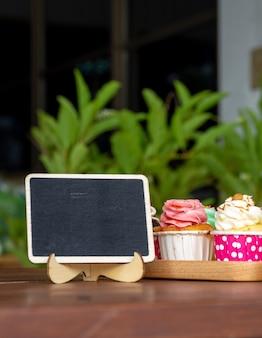 Bunt vom selbst gemachten kleinen kuchen auf hölzernem behälter mit leerer tafel- und kopienraum für ihr