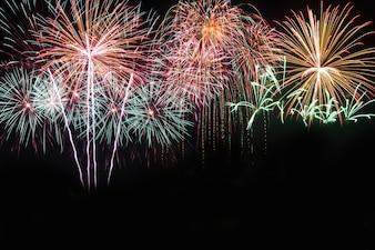 Bunt von den Feuerwerken im Festival des neuen Jahres des Feiertags auf schwarzem Himmel.