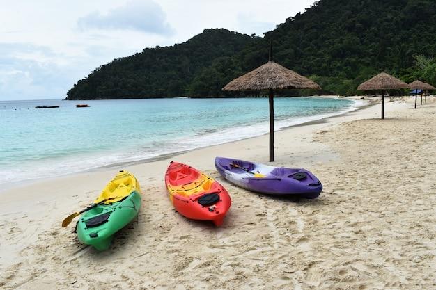 Bunt von den kajaks stehen auf einem sandigen strand in den ferien.