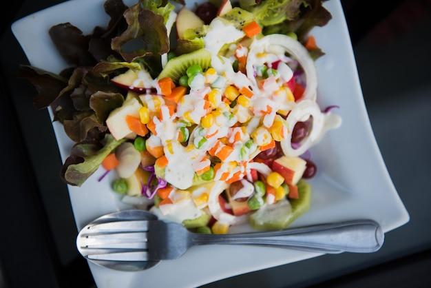 Bunt von den salatrezepten in der weißen platte für abendessen - gesundes lebensmittelkonzept.