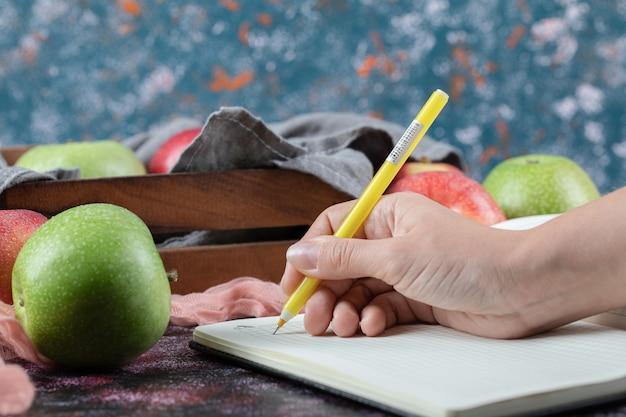Bunte äpfel und ein rezeptbuch beiseite