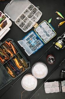 Bunte angelausrüstung mit angelrute auf schwarzem hintergrund