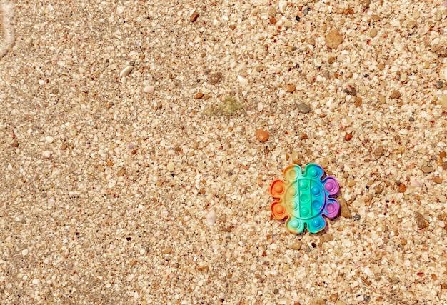Bunte anti-stress-sensorik-spielzeug auf sand mit wasser am strand. sommer- und entspannungskonzept. autismus braucht silikon-stressabbau-spielzeug