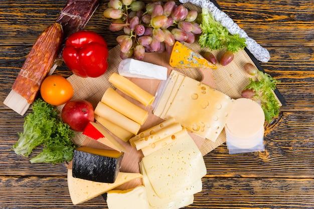Bunte anzeige verschiedener käsesorten auf einem buffettisch in keilen und scheiben mit frischen trauben, roter paprika, tomaten und oliven, draufsicht