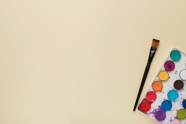 Bunte aquarellpalette und -pinsel auf beige hintergrund