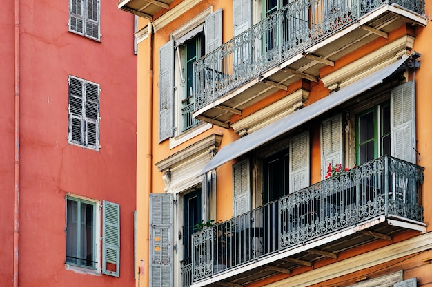 Bunte architektur der fenster und balkone eines roten gebäudes in nizza, frankreich