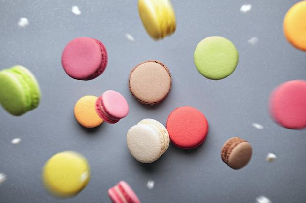 Bunte assroted macarons in bewegung, die mit puderzucker auf grauem hintergrund fallen