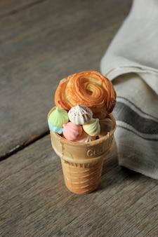 Bunte baiser- und blumencroisant mit eistüte auf rustikalem holztisch, konzept für vintage-bäckerei. platz für text kopieren