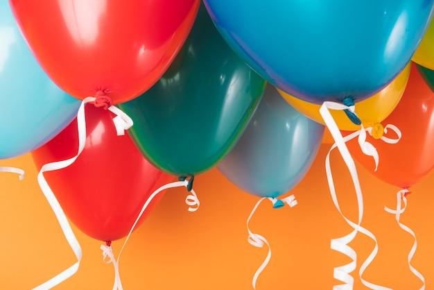 Bunte ballone auf orange hintergrund