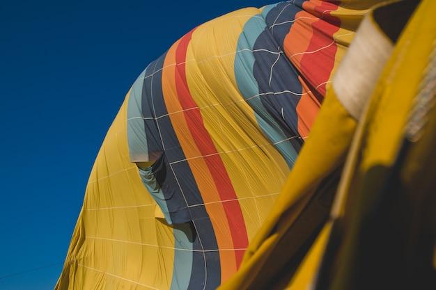 Bunte ballone, die über berge und mit blauem himmel fliegen