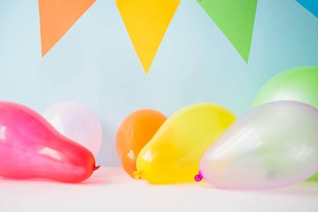 Bunte ballone und flagge gegen blauen hintergrund