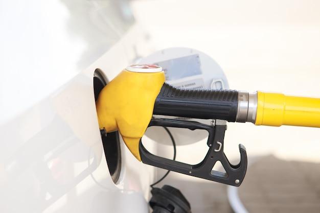 Bunte benzinpumpenfülldüsen lokalisiert auf weißem hintergrund, tankstelle in einem dienst im warmen sonnenuntergang