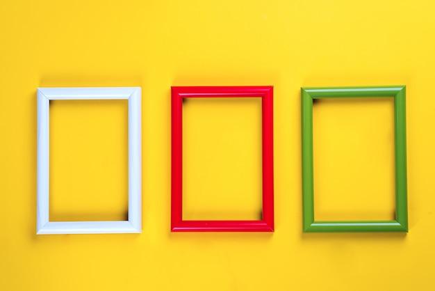 Bunte bild- oder fotorahmen auf einem gelben papierhintergrund. exemplar flach zu legen