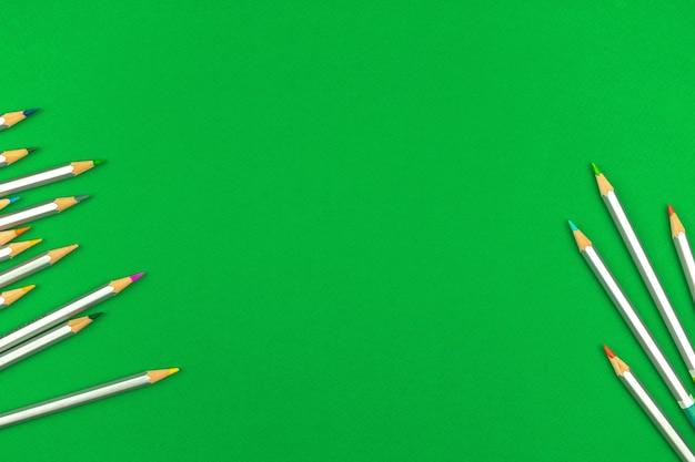 Bunte bleistifte auf einem grünen schultisch. draufsicht und flacher lat-hintergrund mit kopienraumfoto