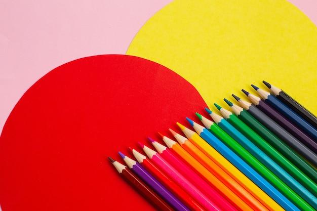 Bunte bleistifte des regenbogens auf kreativem farbigem hintergrund. kunstvermittlungskonzept.
