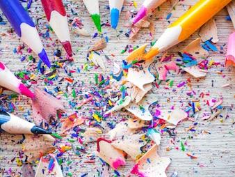 Bunte Bleistifte mit bunten Bleistiftschnitzeln auf hölzernem Hintergrund