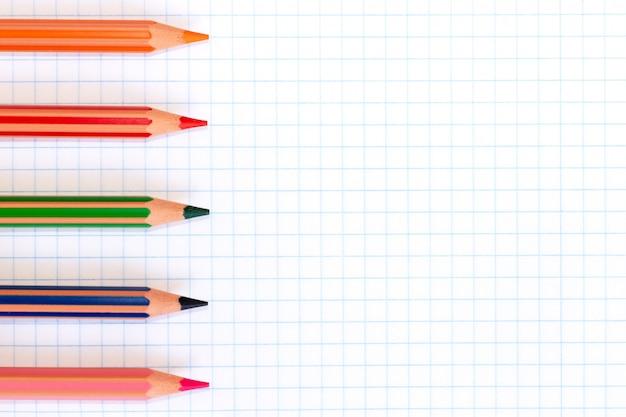 Bunte bleistifte von roten, grünen, orange, rosa und blauen farben auf einem karierten übungsbuch